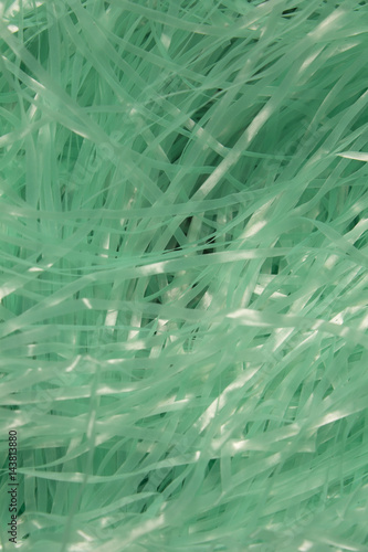 This is a photograph of Turquoise shredded plastic fake Easter grass background