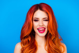 close up portrait of  funny attractive pretty girl with long ginger fair hair put out her tongue while standing on blue background - 143818880