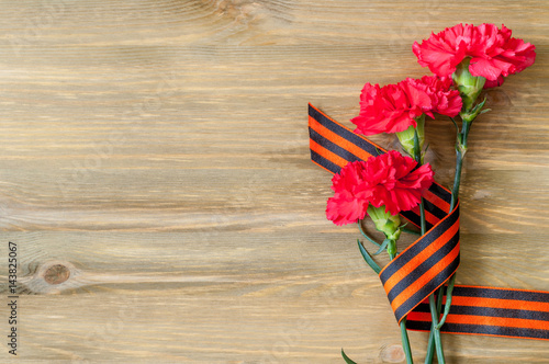Poster 9 May background - red carnations and George ribbon lying on the wooden backgrou