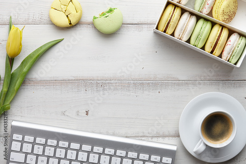 Woman's flat lay workspace with keyboard, macarons, yellow tulips and a cup of c Poster