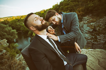 Professional barber shaving his client on the edge of a mountain