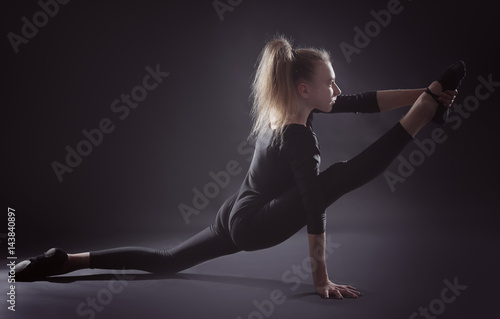 Tuinposter Gymnastiek Young girl doing gymnastics on dark background