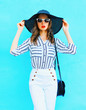 Fashion portrait young woman wearing straw hat, white pants over colorful blue background posing in the city
