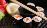 Sushi rolls with salmon, soy sauce and chopsticks