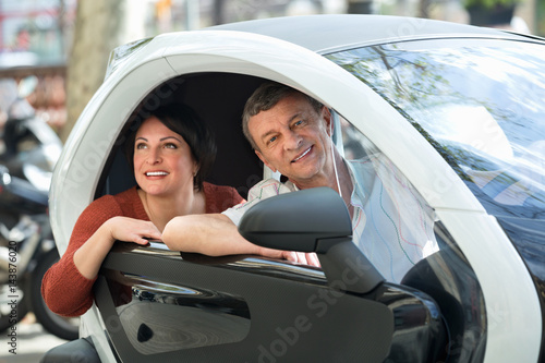 Poster  Adult couple sitting in twizy electric