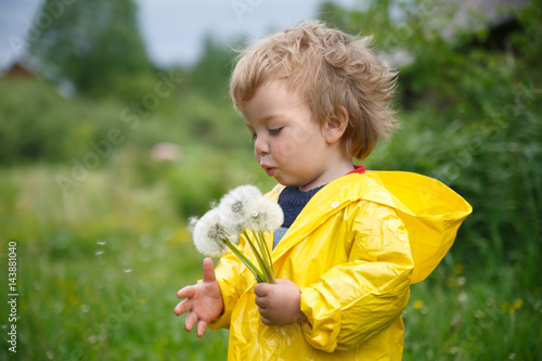 A small child in a yellow raincoat blows a bouquet of couch potatoes on a summer day.