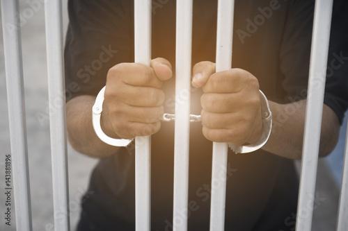 Poster Human hand of prisoner on steel lattice close up.