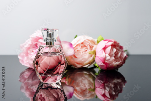 Pink perfume bottle with flowers on black and white background