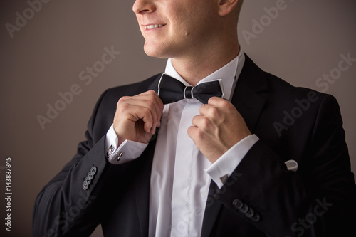 Man in tuxedo holding bow tie  Poster