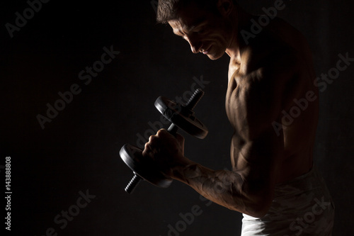Wall mural muscular man holding a weight on a dark background