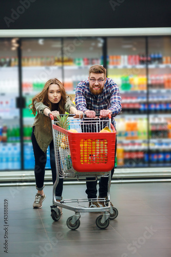 Young Happy Couple With Food Cart Doing Groceries Shopping