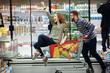 Beautiful couple having fun while choosing food in the supermarket