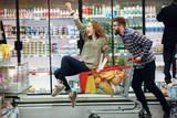 Fototapety Beautiful couple having fun while choosing food in the supermarket