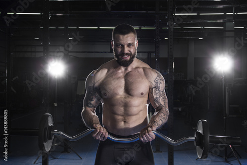 Muscular  Man Doing Heavy Weight Exercise For Biceps With Barbel Poster
