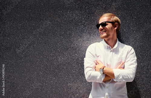 Poster Handsome confident caucasian young man in sunglasses and white shirt leaning on grey wall
