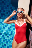 Enjoying suntan and vacation. Colorful portrait of pretty young woman in red swimsuit lying near swimming pool. - 143896840