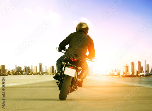 Poster rear view of man riding motorcycle on urban traffic road for people leisure trav