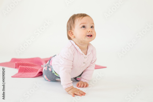Poster Baby girl sitting on floor isolated over white background