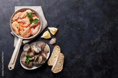 Fototapeta Fresh seafood on stone table. Scallops and shrimps