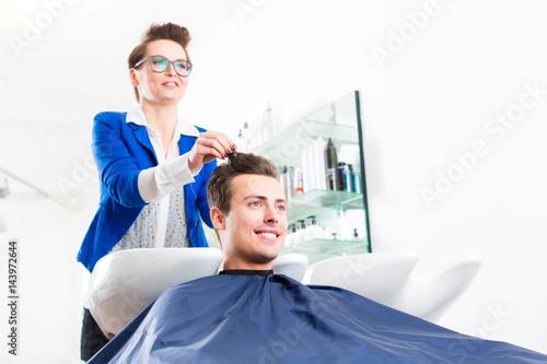 Friseur schneidet Mann die Haare im Herrensalon