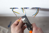 Electrician stripping insulation from wire for installation an electrical outlet - 143987820