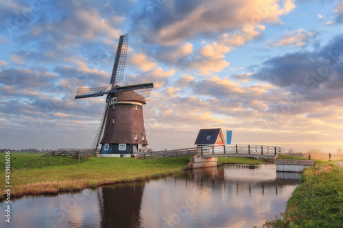 Windmill near the water canal at sunrise in Netherlands Canvas