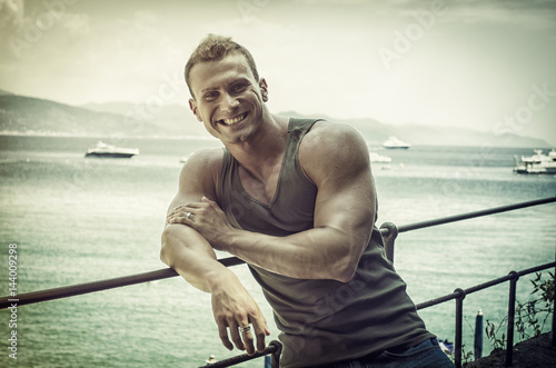 Juliste Handsome young muscle man at the seaside, outdoors, in front of the sea