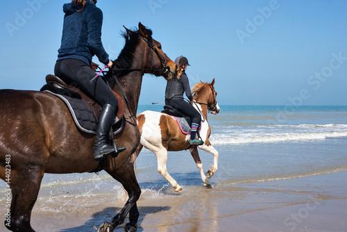 Poster cavalière au galop sur la plage