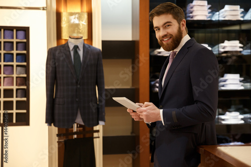 Cheerful man in suit with tablet in wood room