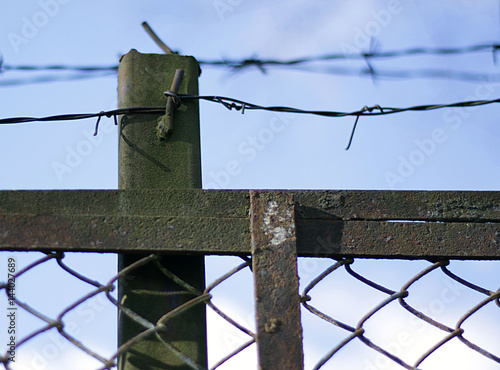 Poster Barbed wire above the fence