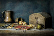 Classic still life with old book placed with vintage jar,wooden savings box,nuts and cup of coffee on rustic wooden background..