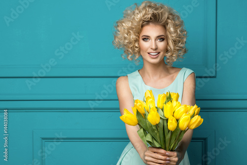 Beautiful blonde girl in the blue dress with flowers tulips in hands on a turquoise background