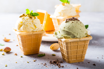 Pistachio ice cream with grated chocolate in waffle cups on gray stone background. Homemade summer food concept.