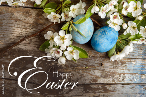Happy Easter background with blue painted easter eggs, white flowers on wood bac Poster