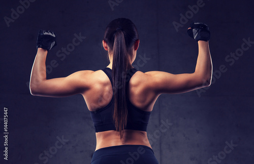 young woman flexing muscles in gym Poster