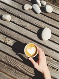 Having coffee latte take away in paper cup disposal, outdoor sunny day, wooden table - 144078429