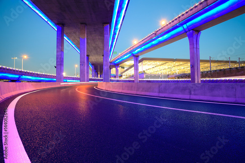 Empty road floor with city viaduct bridge of neon lights night Poster