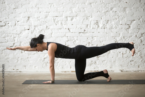 Poster Young yogi attractive woman practicing yoga concept, standing in Donkey, Kick ex