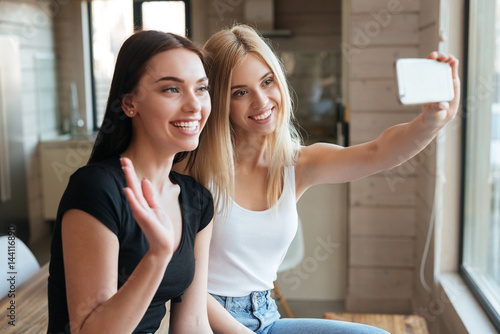 Two cheerful women indoors using mobile phone and waving