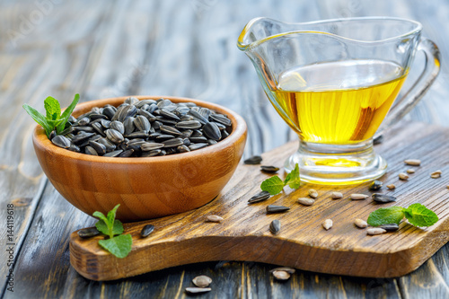 Oil and sunflower seeds in a wooden bowl.