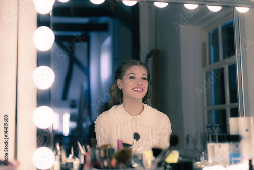Poster Smiling pretty young woman retro 1940s style looking in theater mirror