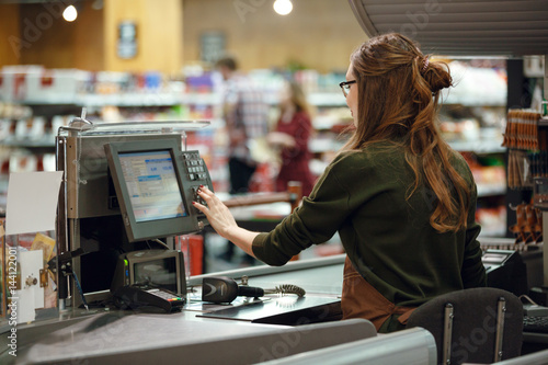 Cashier woman on workspace in supermarket shop