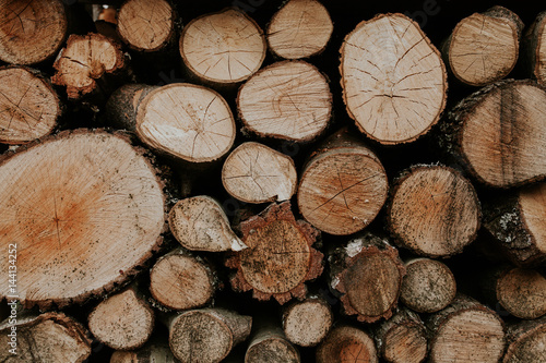 Papiers peints Texture de bois de chauffage Pile of natural wooden wood. Cross-sectional image of firewood, front view. Woodpile of cut trees in the lumberyard. Background and texture with space for text or image. Fire wood prepared for winter.