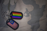army blank, dog tag with flag of malaysia and gay rainbow flag on the khaki texture background. military concept