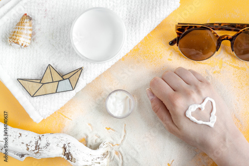 Woman cosmetic set with sun protection lotion orange background top view © 279photo