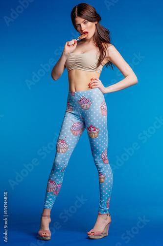 Slender model girl in Studio on dark blue background with Lollipop in full-lengt Poster