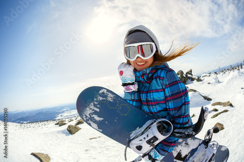 obraz lub plakat Girl snowboarder enjoys the ski resort
