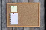 Fototapety White memo pad and post-it on cork board over wood background