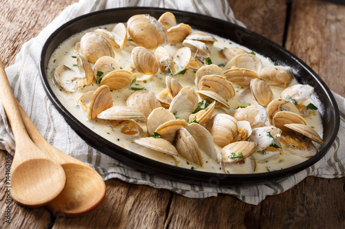 Delicious clams in a creamy sauce with parsley closeup on a plate Poster