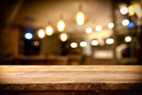 wooden table in front of abstract restaurant lights background - 144181039